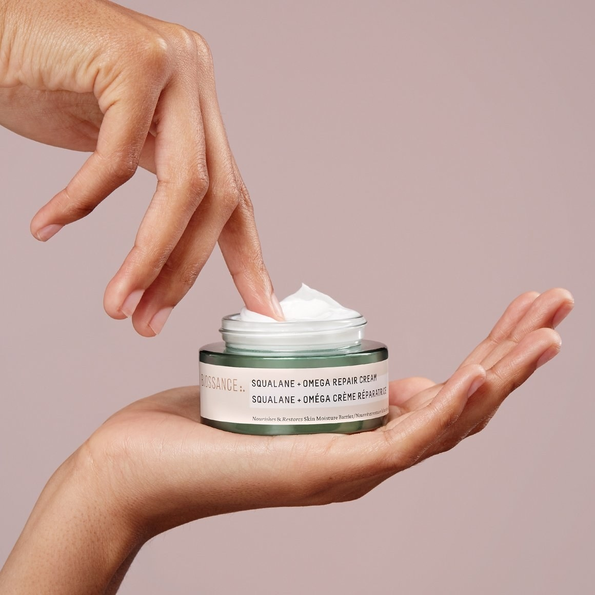 Model's hand scooping out a bit of the whipped-textured moisturizer from the jar