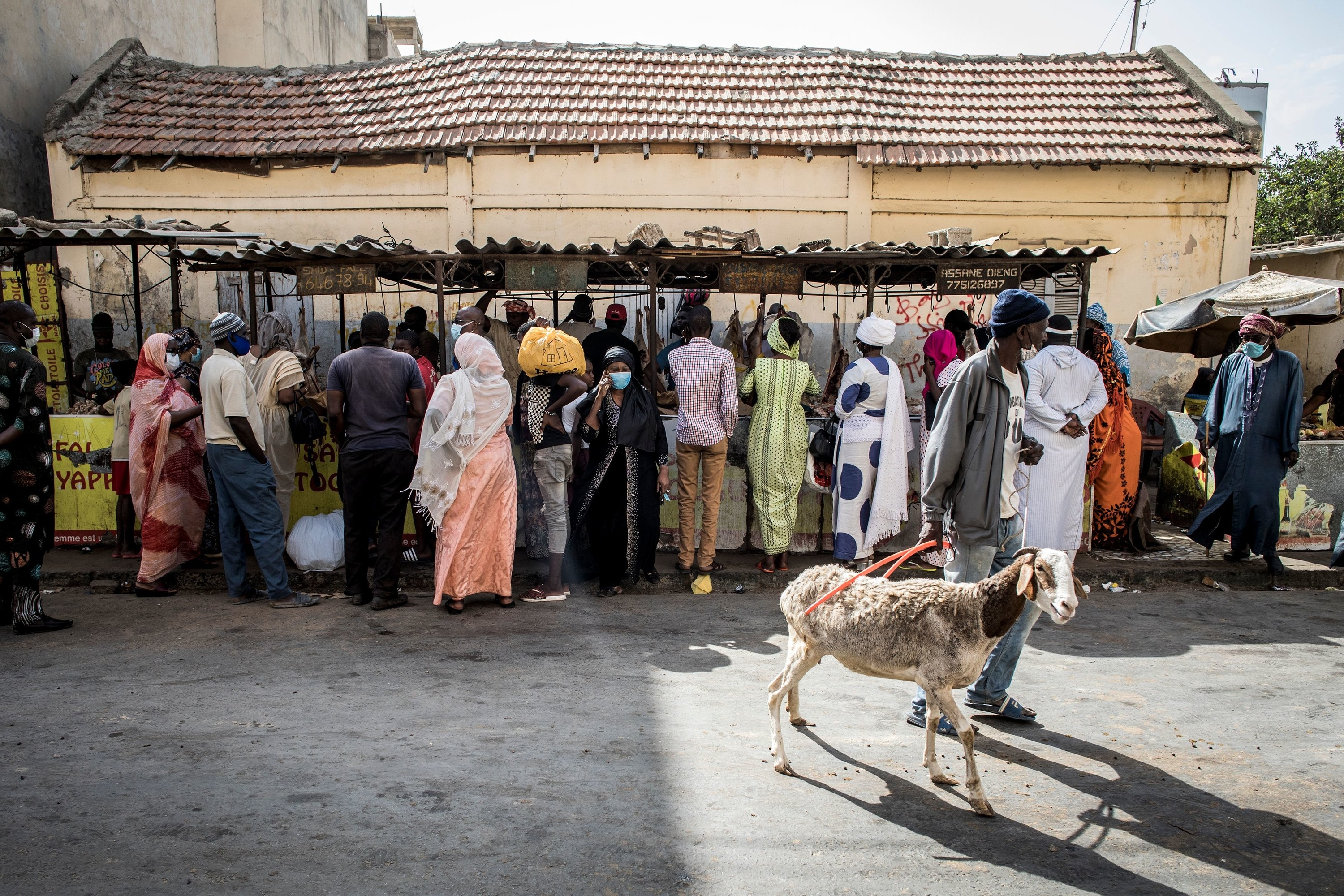 People stand in front of a stall at an outdoor market