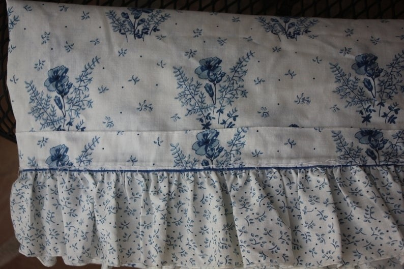 A blue and white flower pillow case with a ruffle