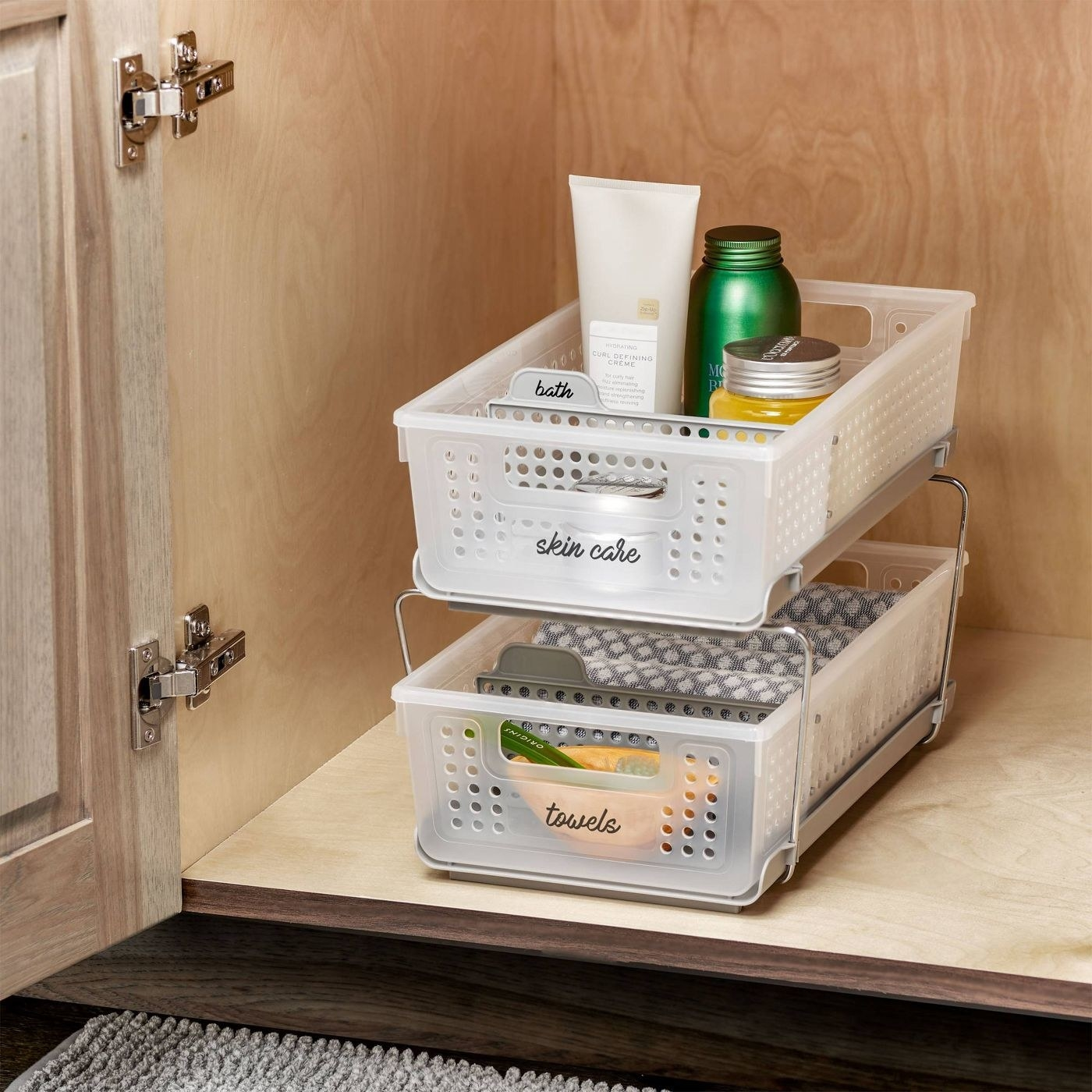 The Madesmart Two-Tier Organizer with Dividers in Frost/Gray storing toiletries in a bathroom cabinet