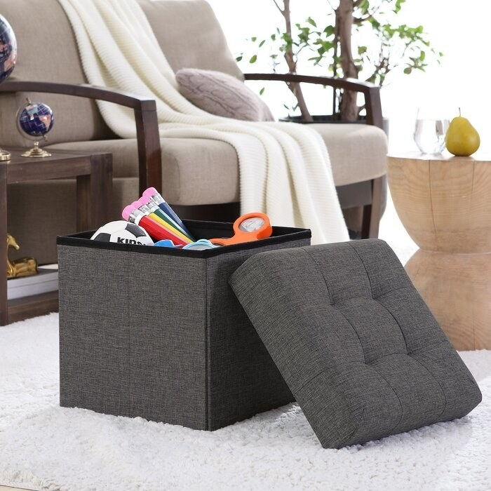 The Charcoal Lambertville Foldable Tufted Square Cube Foot Rest Storage Ottoman in a living room