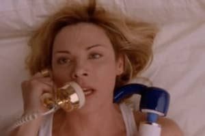"""Samantha from """"Sex and the City"""" on the phone in bed."""