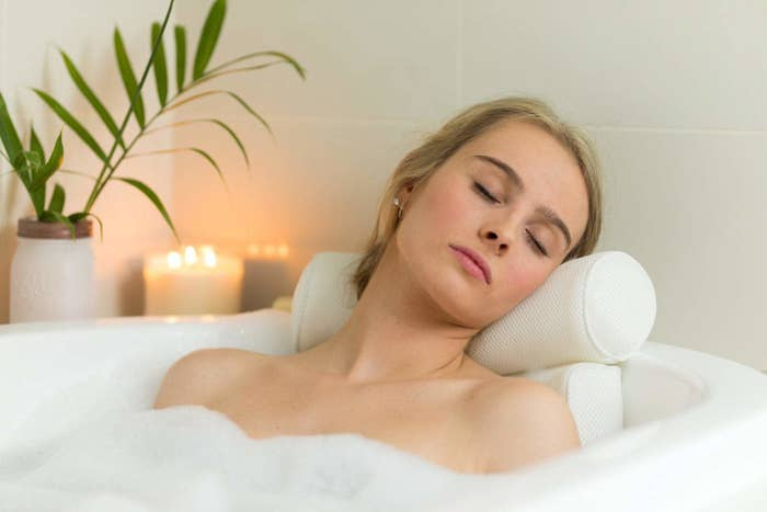 Person resting head and shoulders on mid-century-modern style bath pillow while soaking in bubble bath