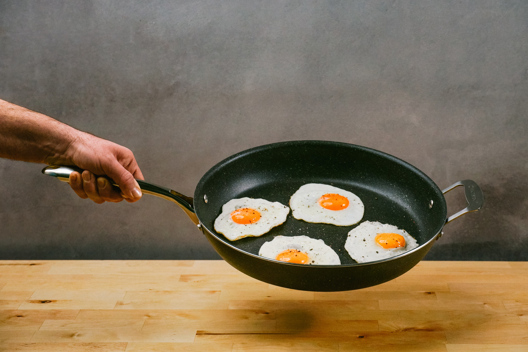 person holding a black nonstick skillet with four eggs in it