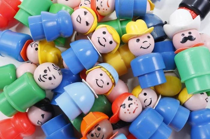 A pile of plastic Fisher-Price Little People from the 1980s