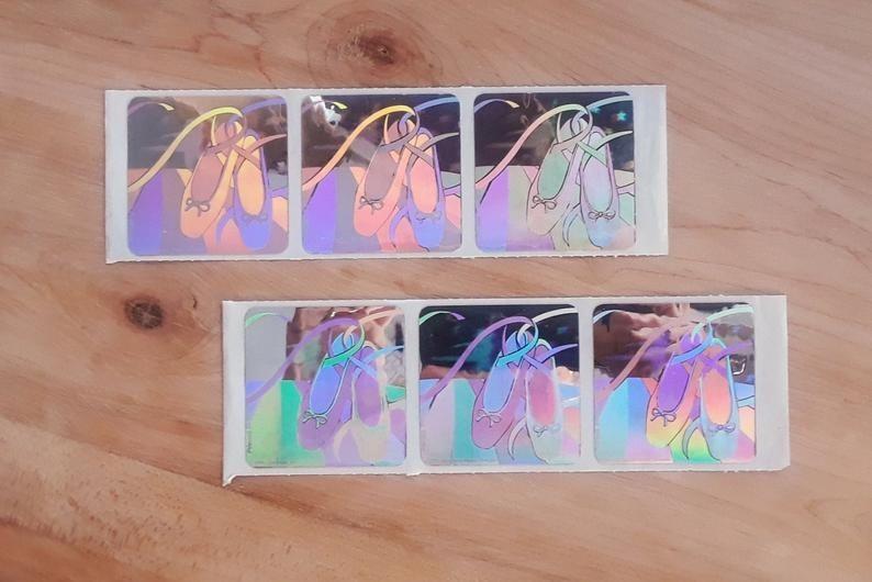 Six iridescent SandyLion ballet slipper stickers still on the sticker strip