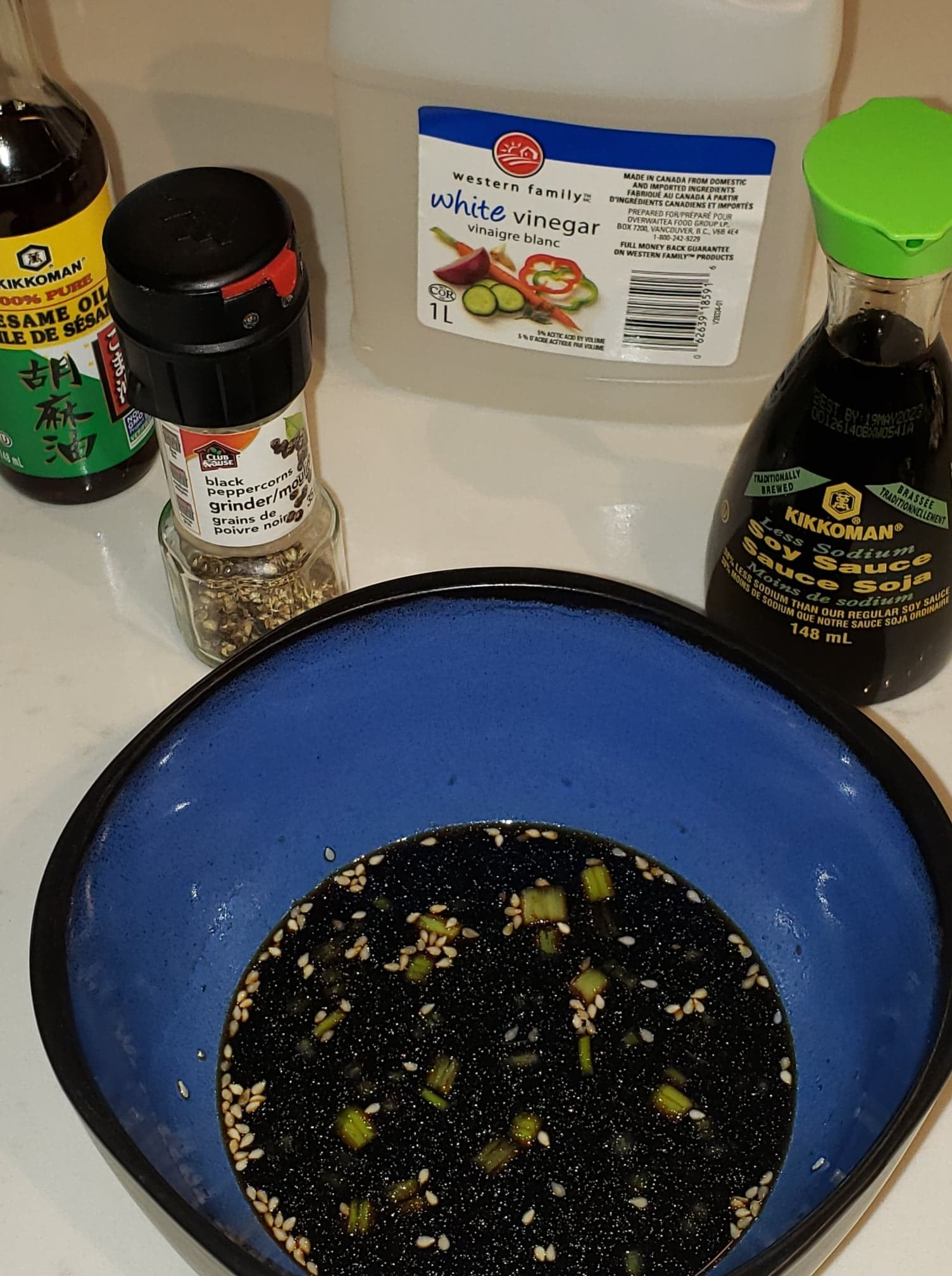 A bowl of the finished dipping sauce next to bottles of sesame oil, soy sauce, black pepper, and white vinegar