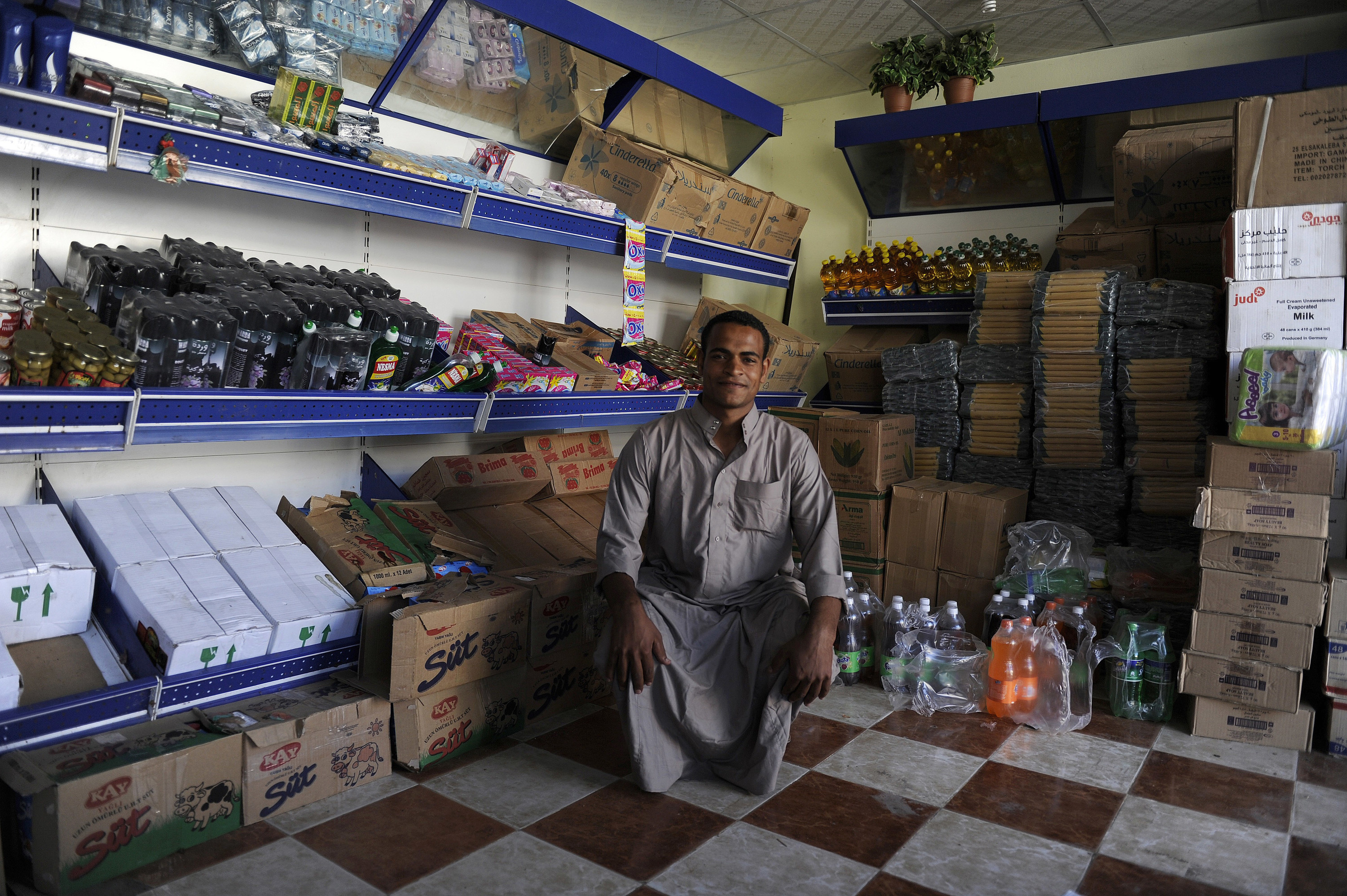 A vendor sits in the interior of a small grocery store