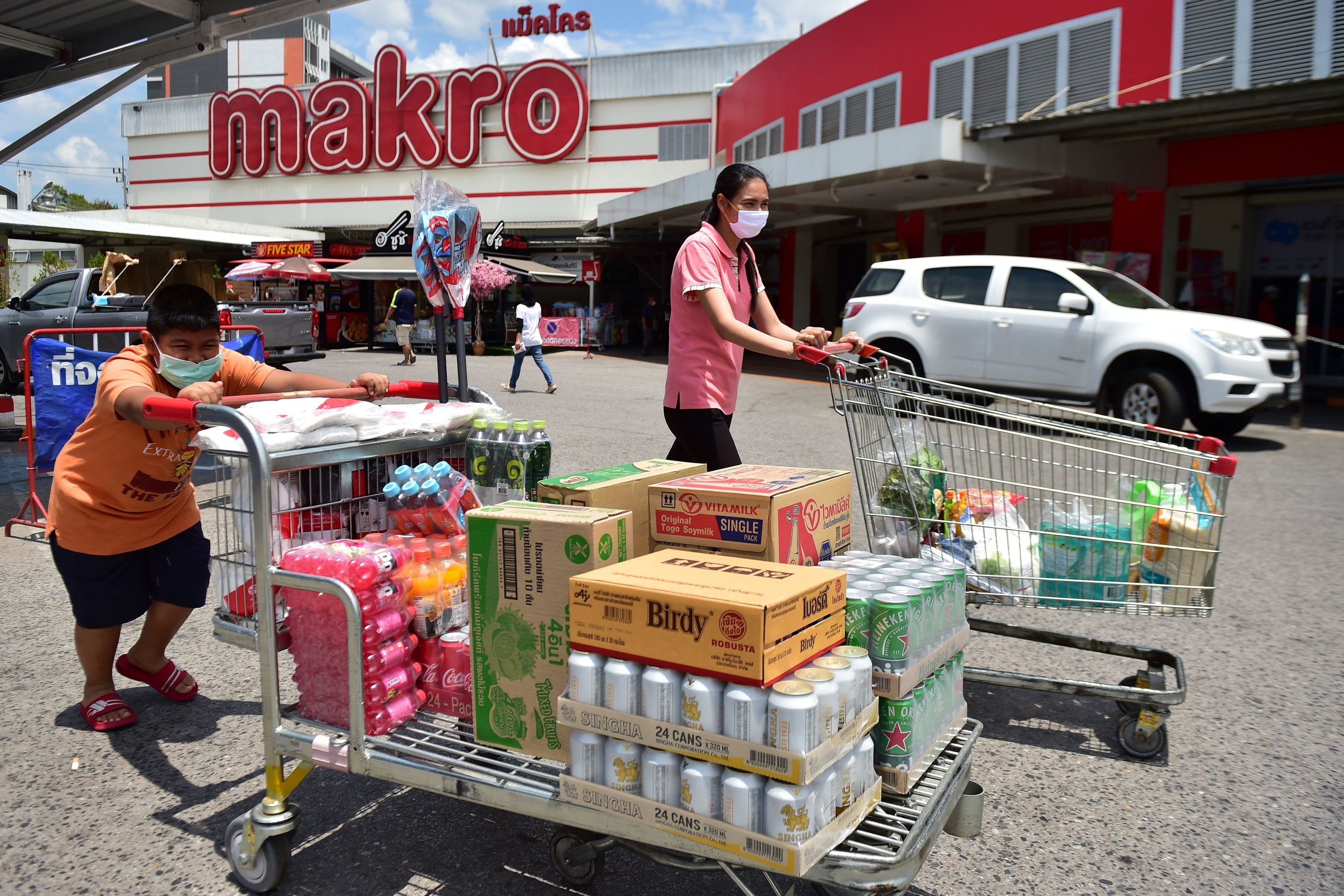 A child and a woman have full carts outside a Makro supermarket