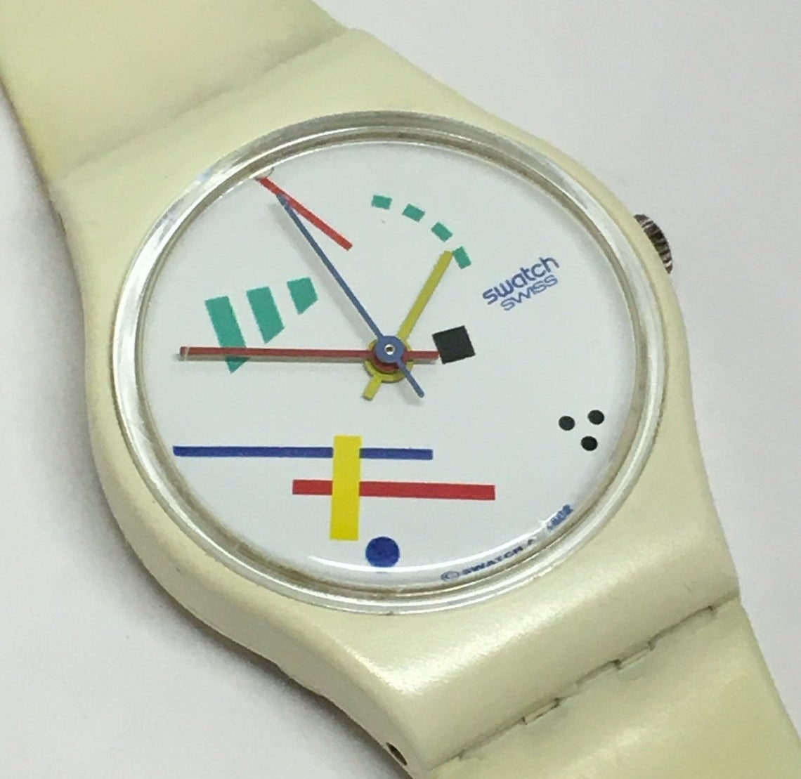 A close up of the face of a Swatch Watch