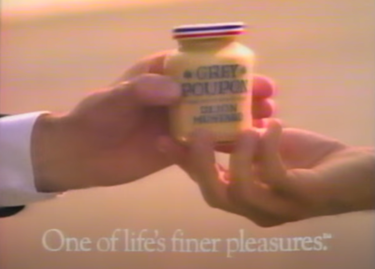 """A screenshot of one hand handing another hand a jar of Grey Poupon with """"One of life's finer pleasures"""" written underneath it from the commercial for it"""