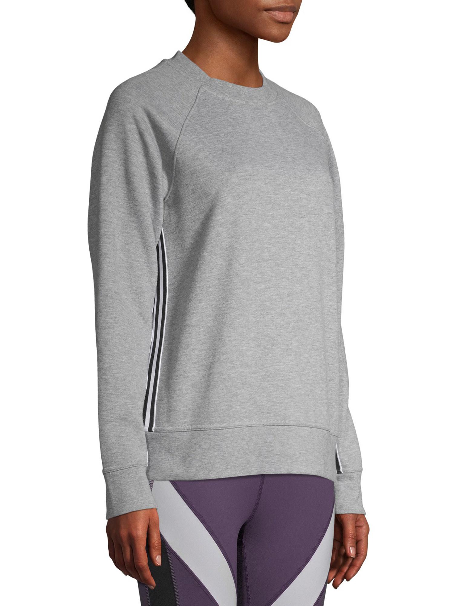 person wearing a gray crewneck sweatshirt and purple leggings