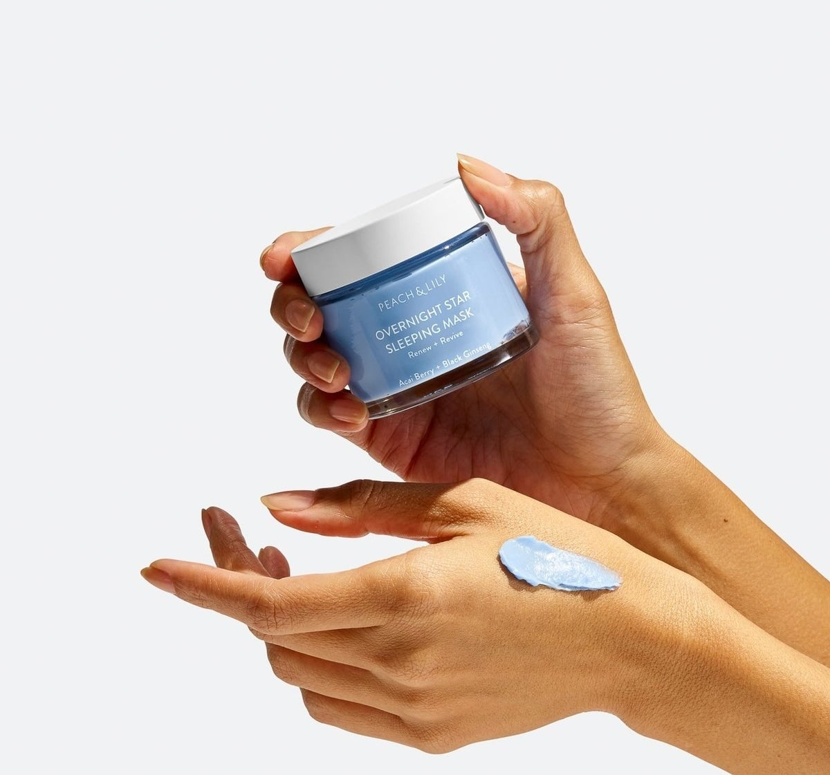the tub and a swatch of the cream on a hand, showing its blue color and thick smooth texture