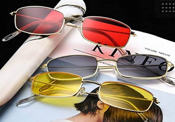 Three thin-rimmed retro sunglasses in the colours red, black and yellow displayed on a magazine.