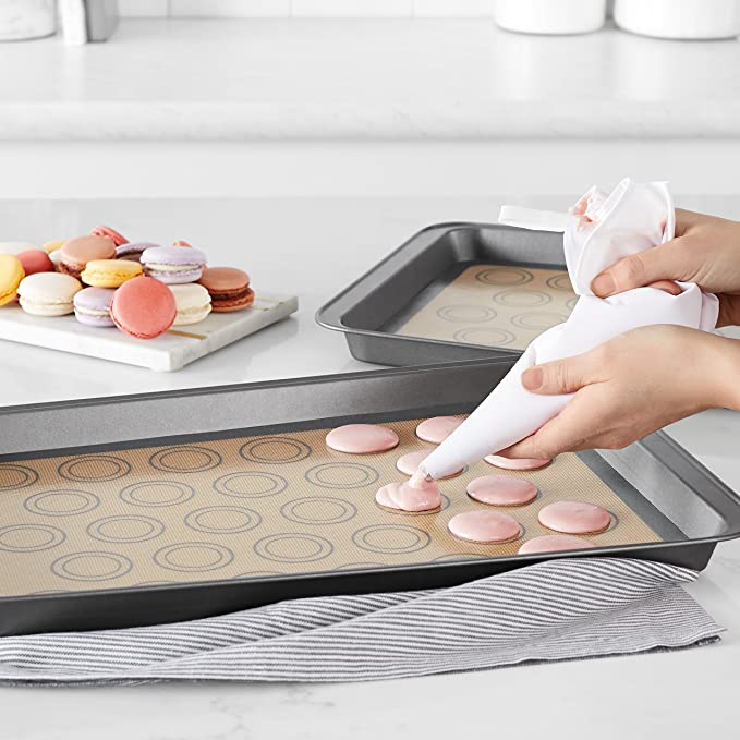 A person making macaroons on the baking sheet