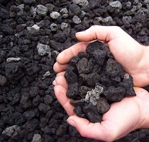 Black volcanic rocks held in a hand.