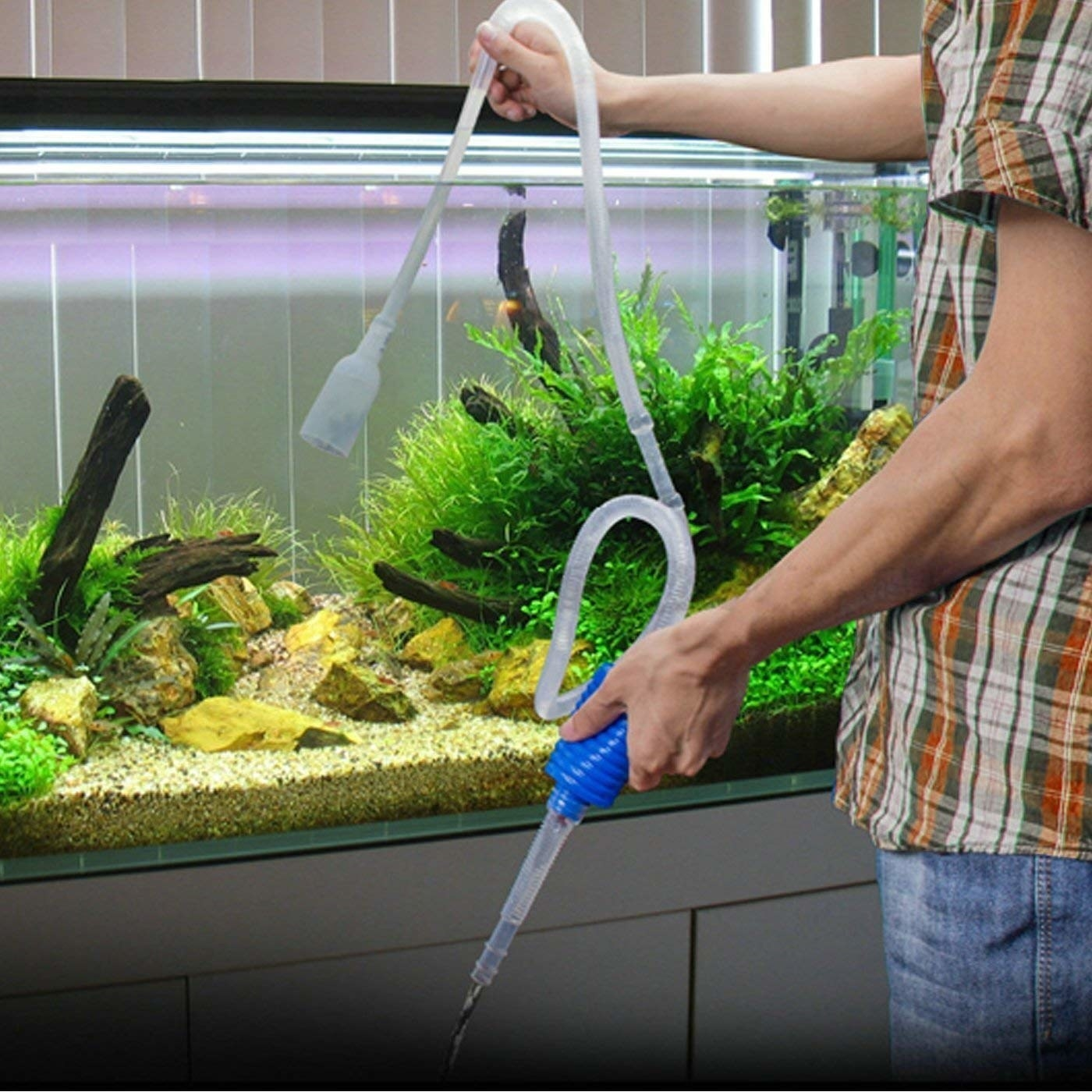 A person changing the water in the tank using the pump.