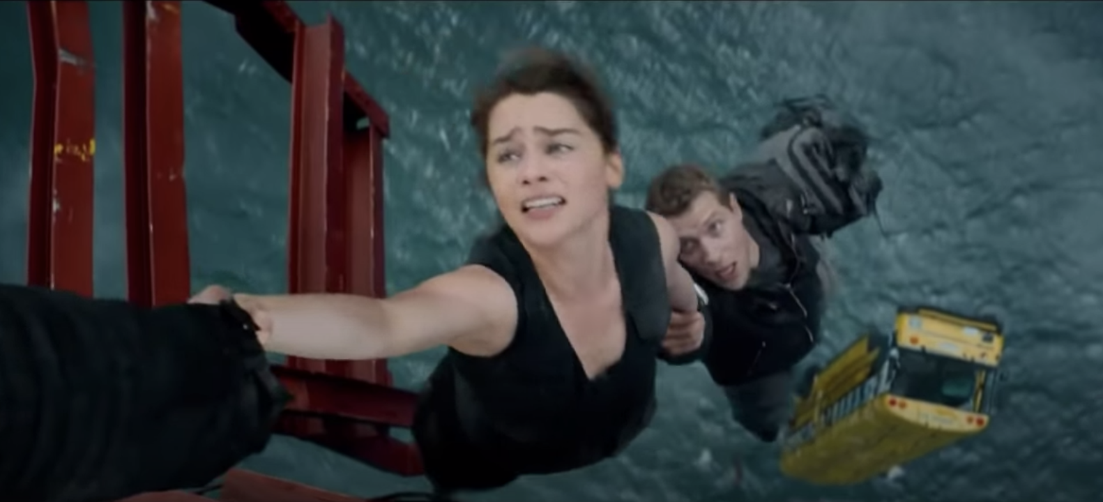 Emilia Clarke hangs off the side of a bridge and holds someone's hand for dear life