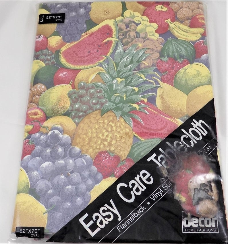 A vinyl table cover that features various fruits on it and still in the original packaging