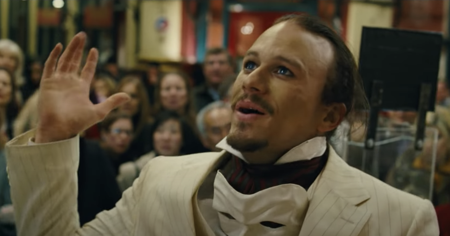 Heath Ledger in a white suit speaks to a crowd in the film