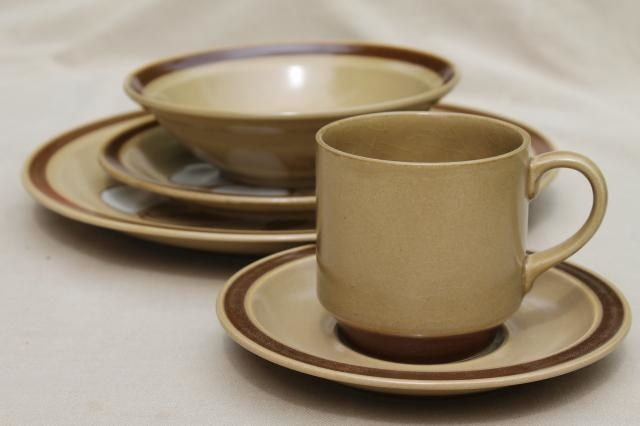 A dinner plate set along with matching coffee cup saucer plate that is tan with a brown trim