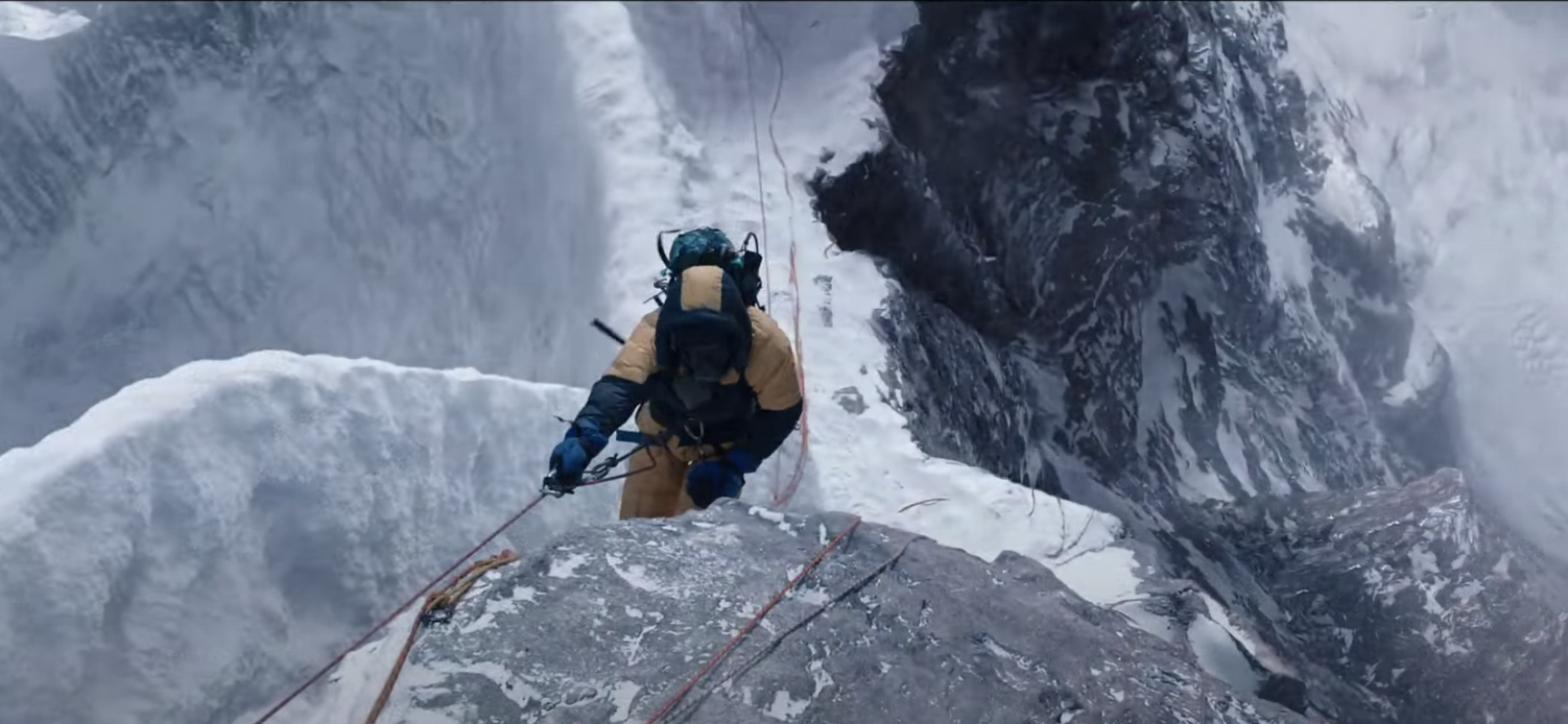 A man climbs to the very top of Mount Everest
