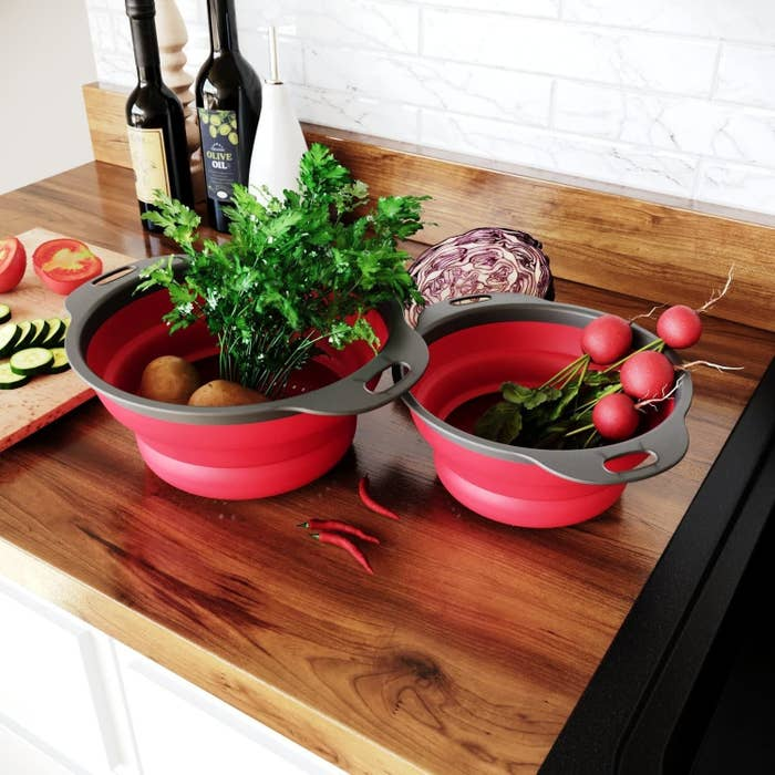 Two collapsible colanders filled with veggies