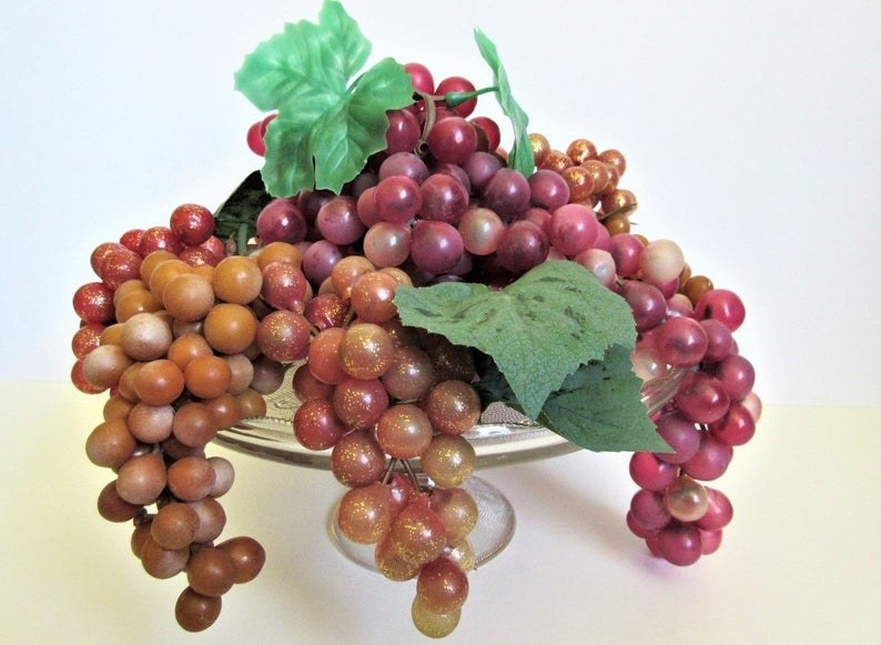 A bowl of fake purple grapes that looks old