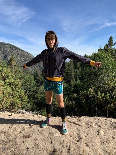 the author wearing a pair of the socks on a hike with woods behind them