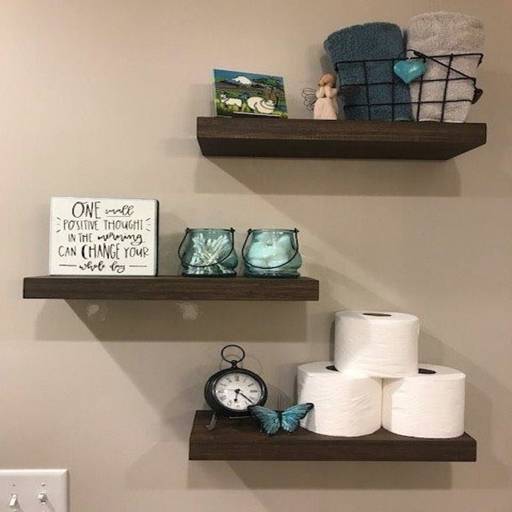 reviewer photo of three shelves in the bathroom with toilet paper, candles, and towels on them