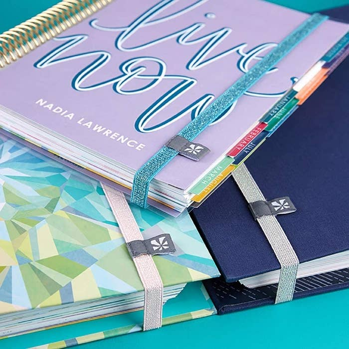 Three planners held together with the elastic bands