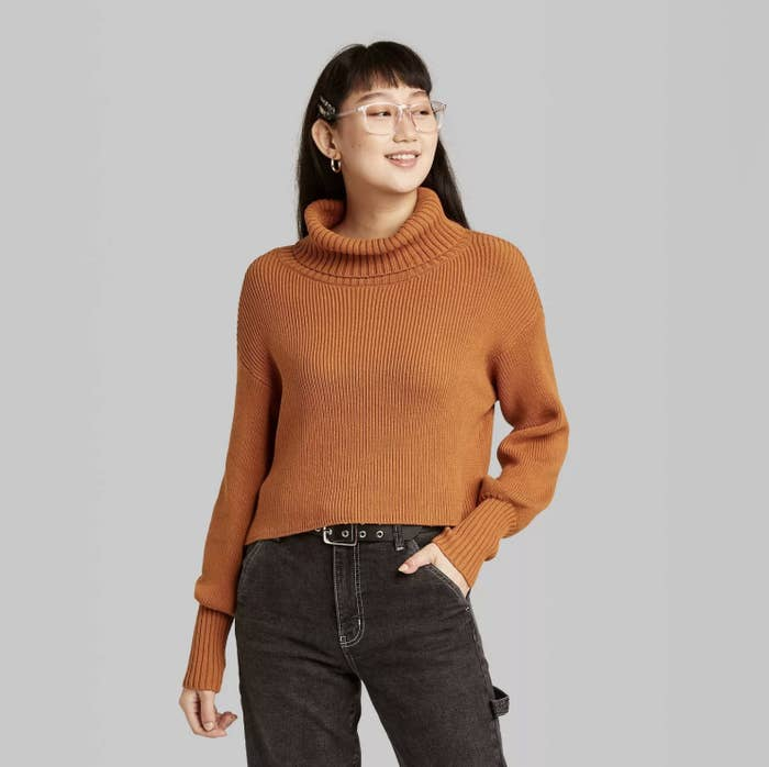 Model is wearing a rust ribbed cropped turtleneck sweater and black jeans.