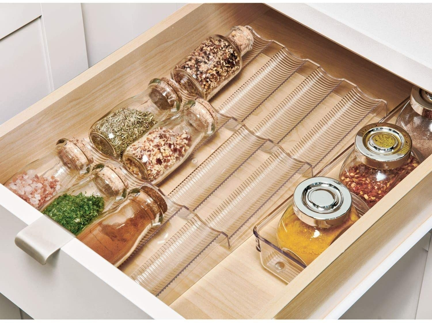 A kitchen drawer with spice bottles organized into rows