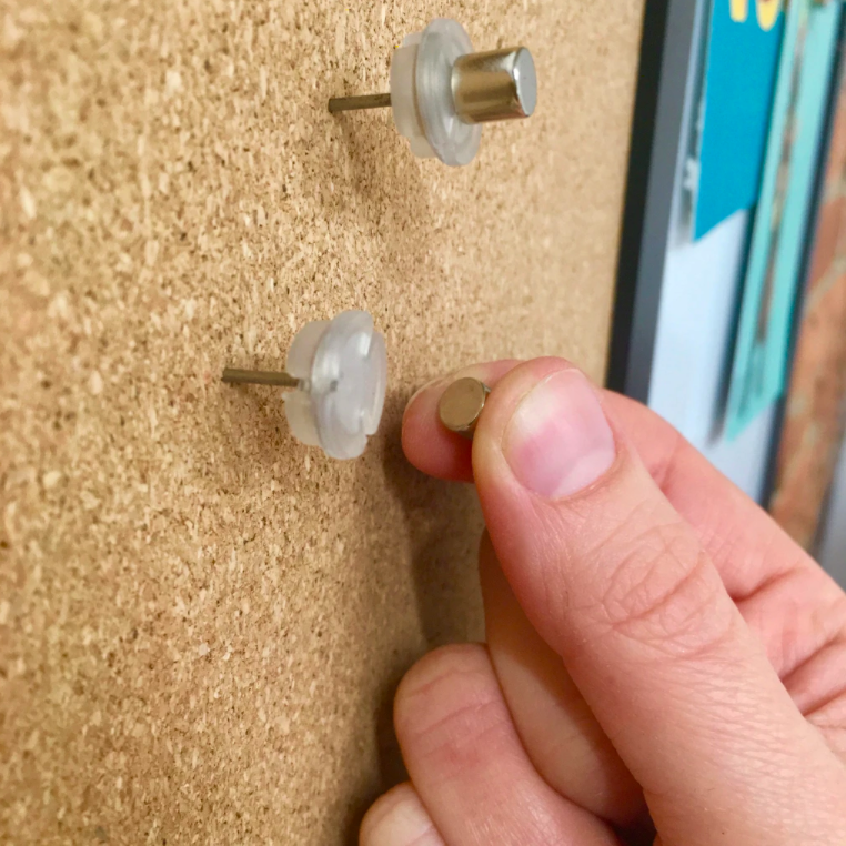 A person holding the magnetic piece next to the pushpin piece