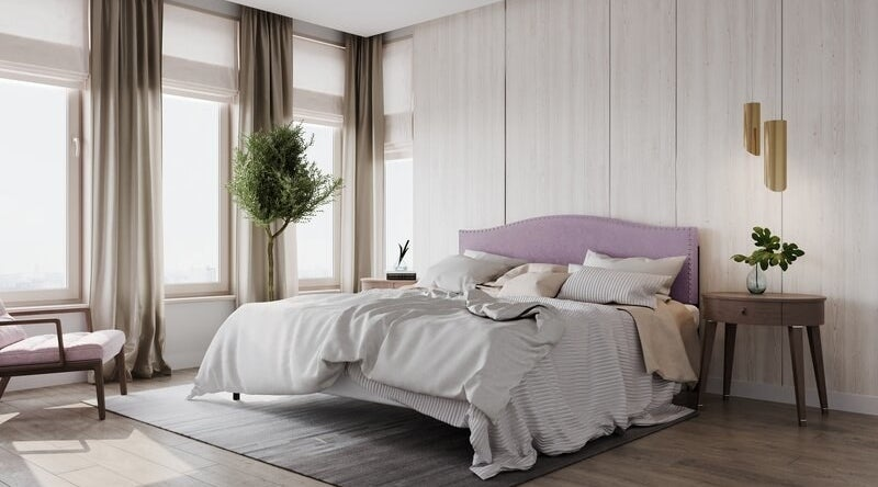 The mauve headboard staged on a made bed