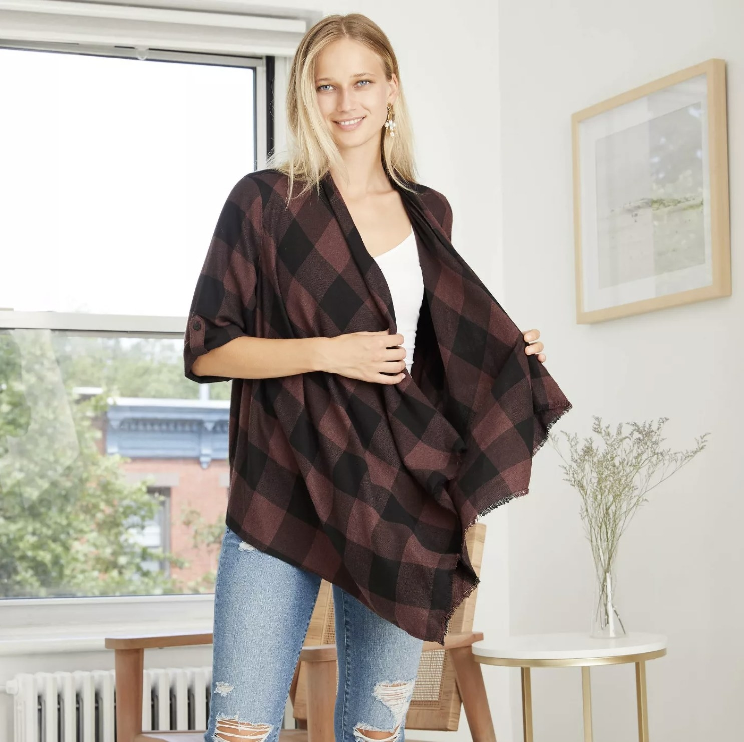 Model is wearing a dark red and charcoal grey flannel kimono over a white tank and light wash blue jeans