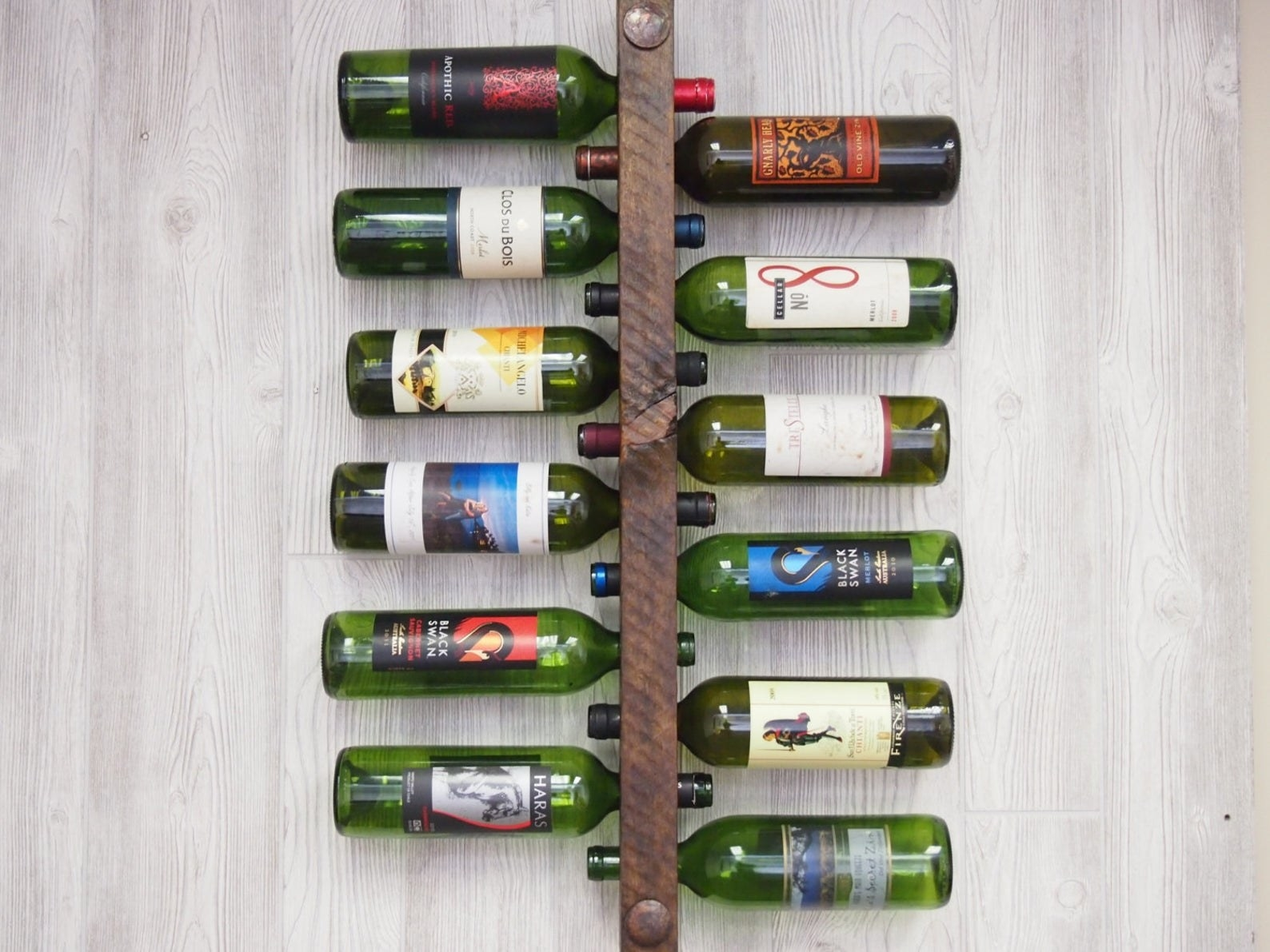A long piece of brown wood with six wine bottles through holes on each side on a wall