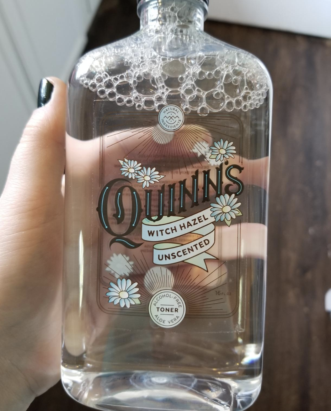 """reviewer holding up clear bottle with black cap labeled """"Quinn's witch hazel unscented"""""""