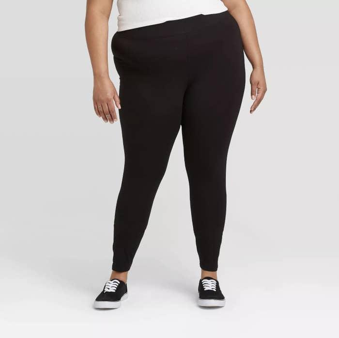 Model is wearing black leggings and black sneakers