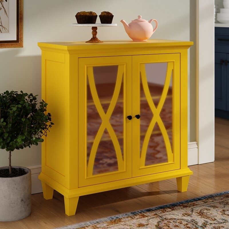 A yellow cabinet with three shelves and glass window doors