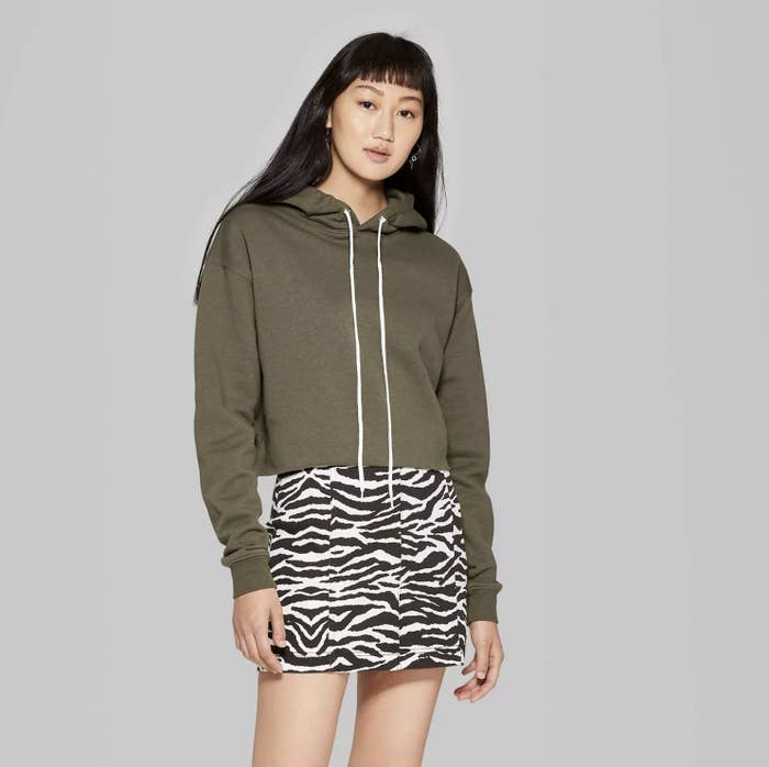 Model is wearing an olive green cropped hoodie with white drawstrings and a zebra print mini skirt