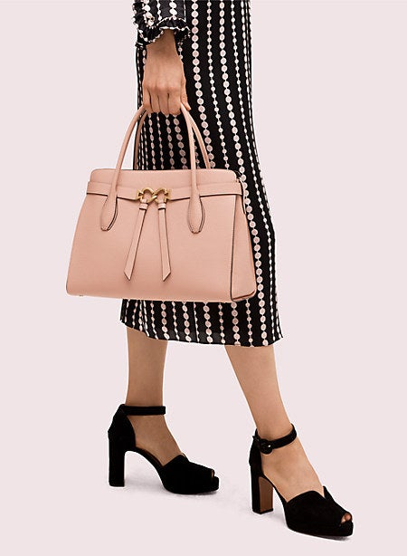 A model carrying a large satchel bag in beige with short handles and a knotted design on front