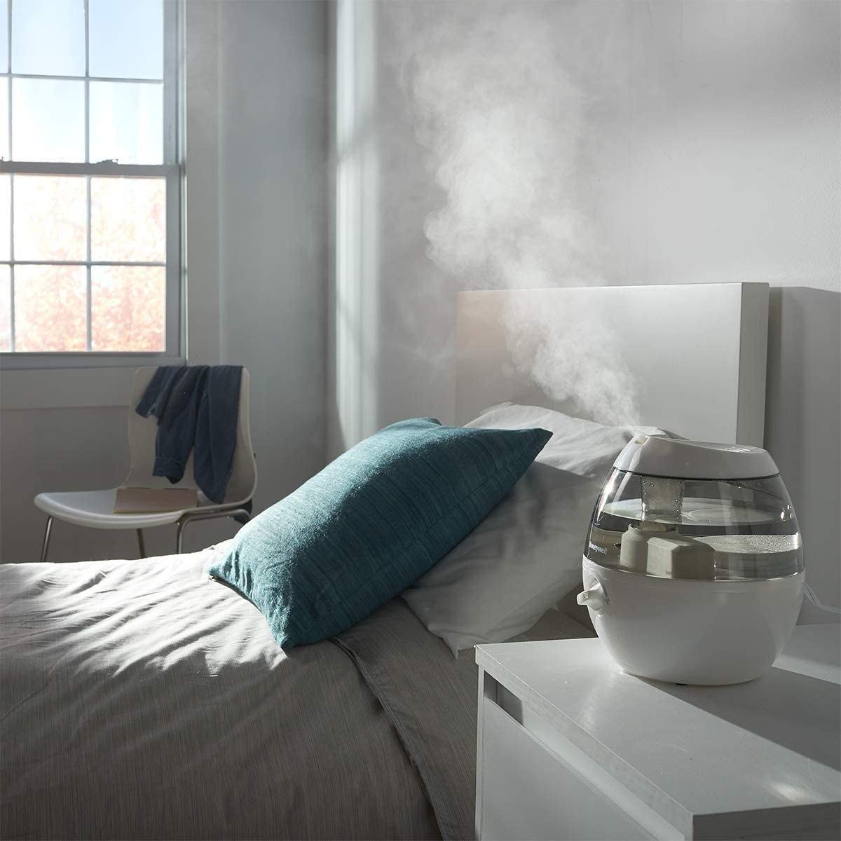 The humidifier on a nightstand, gently misting the room