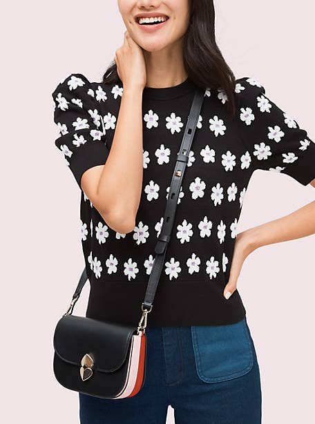 A model wearing the crossbody bag, which is black with pink and red accents on the side and a silver spade on the front