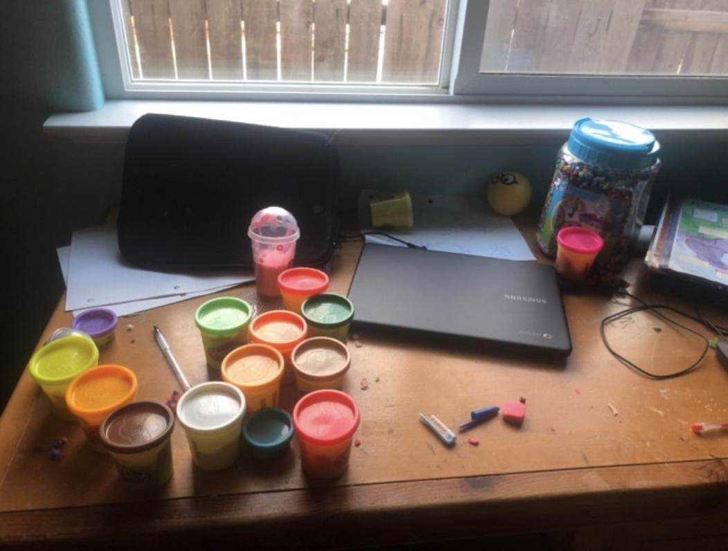 A messy at-home school desk covered in playdough and erasers,