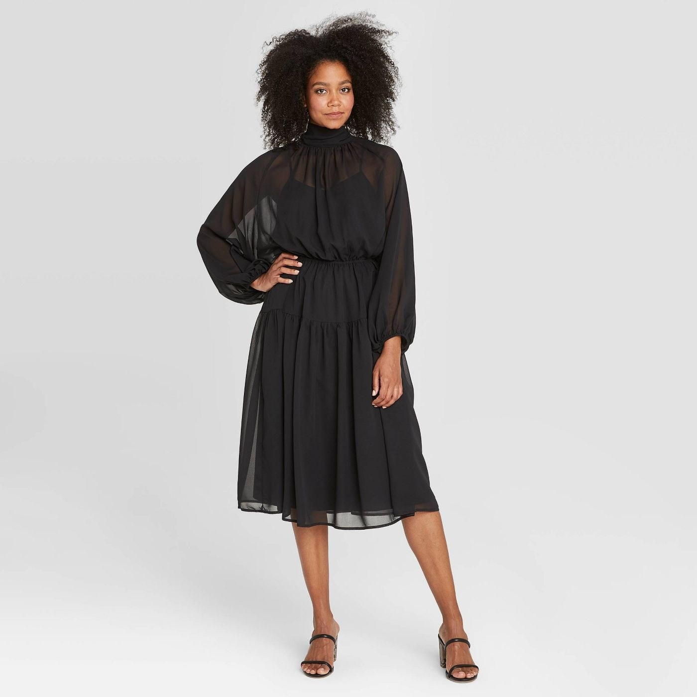 Model in black long sleeve midi dress