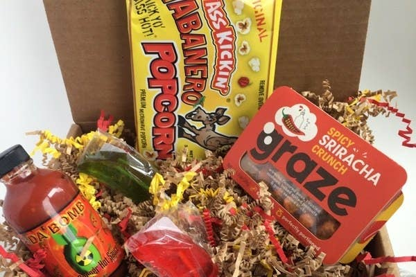 The Scorchin' Hot Box filled with spicy items like a bottle of hot sauce, a Grace spicy sriracha crunch snack, habanero-flavored popcorn, and more