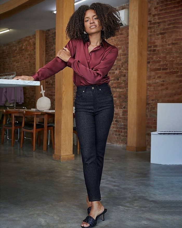 A model wearing the burgundy long-sleeved shirt tucked into dark wash jeans