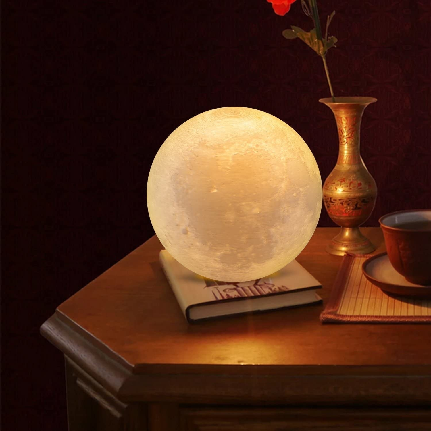 The moon-shaped lamp on a night stand in a dark room