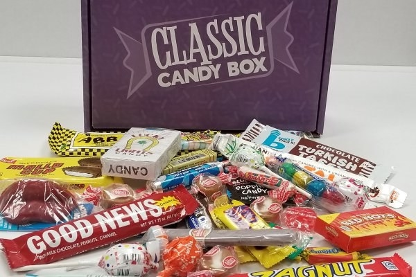 Various assorted candies in front of the Classic Candy Box like Good News, Blow Pops and Tootsie Pops, and Mallo Cups